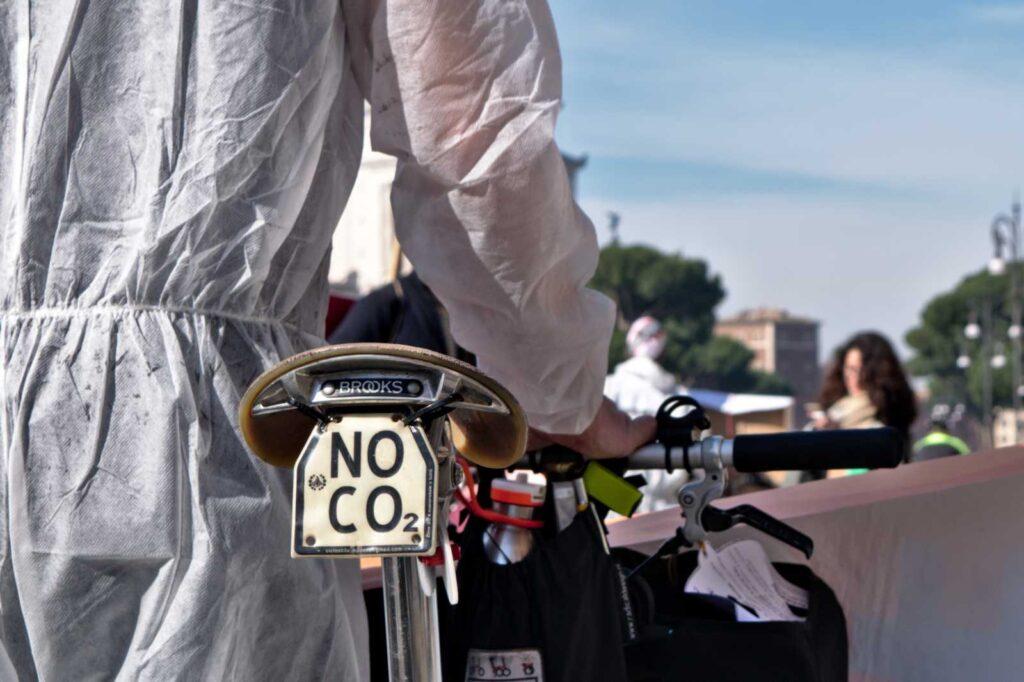 """Cartello """"No CO2"""" su una bicicletta alla manifestazione #bastamortinstrada."""
