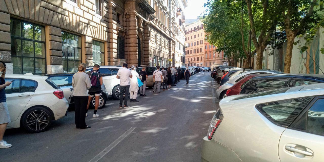 Persone fanno la fila alle poste in strada perché il marciapiede è invaso dalle automobili
