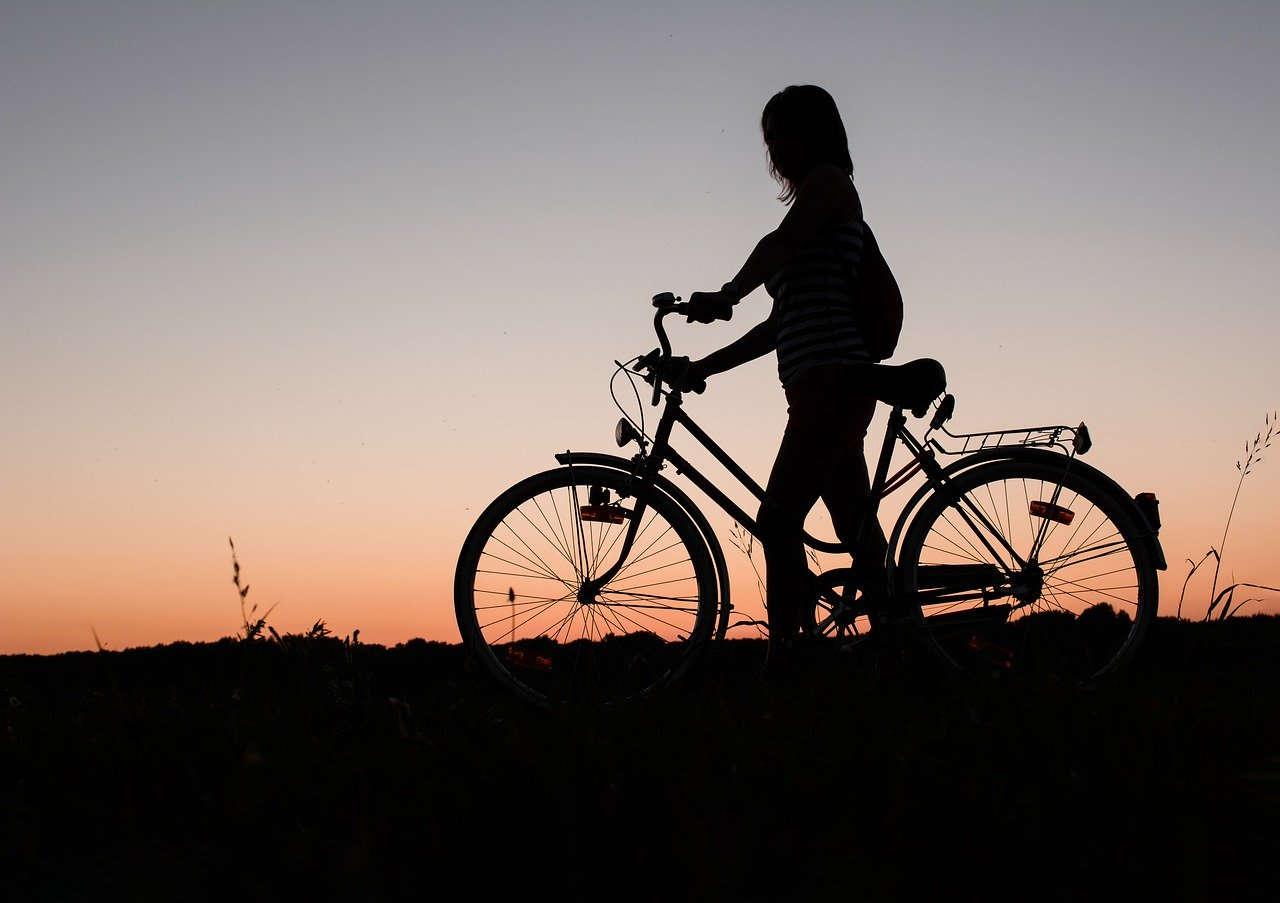 Profilo di ragazza in bici al tramonto